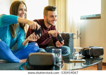 Happy friends playing video games with virtual reality glasses - Young people having fun with new technology console online - Happiness and gaming concept - Focus on man face - Warm filter