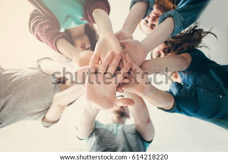 Happy friends putting their hands together.Focus on hands during a sunny day at camera. #614218220