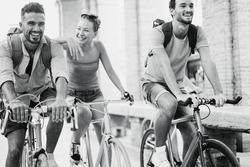 Happy friends riding old style bicycles - Young people having fun together around the city - Youth, friendship and healthy lifestyle concept - Focus on right man face - Vintage editing