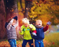 happy friends, schoolchildren having fun in autumn park among fallen leaves