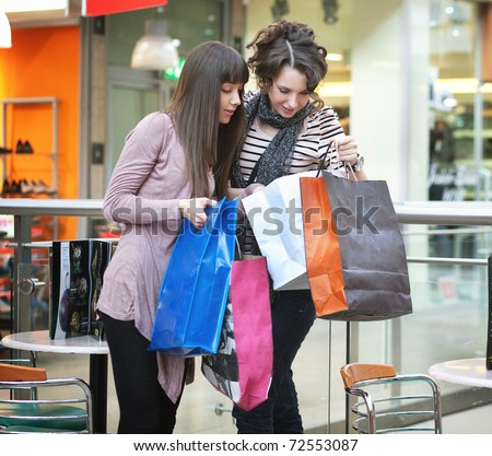 Happy friends showing clothes