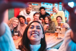 Happy friends taking a group selfie at pub - Group of multiracial millennial people having fun together at pub and taking a photo - Birthday party or after work meeting, happiness and teamwork concept