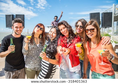 Happy friends taking a self portrait with selfie stick at a open air party - People dancing and partying while the disc jockey mixes two song tracks at a summer concert