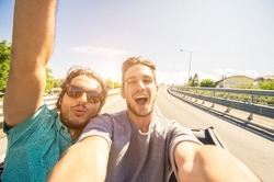 Happy friends taking a selfie at car trip - Two caucasian tourist travelling around the world