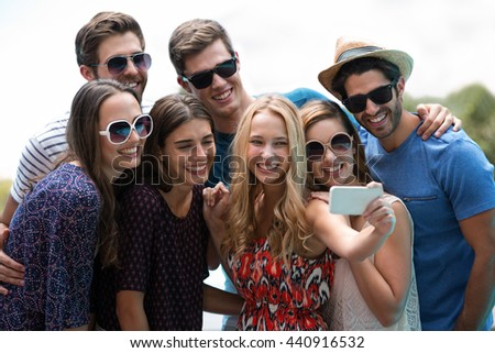 Happy friends taking a selfie near swimming pool on a sunny day