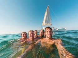 Happy friends taking a selfie with action camera inside the ocean with sail boat in background  - Young people having fun swimming in the sea - Focus on right man - Travel and youth lifestyle concept