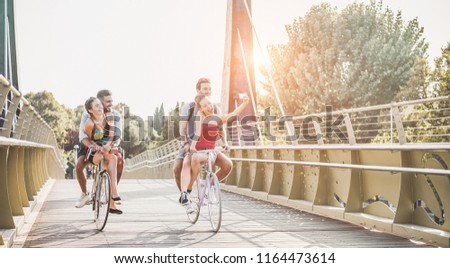 Happy friends taking photo selfie with smartphone on bicycle - Young students having fun together riding a bike - Youth, technology trends and friendship concept - Main focus on right woman face Zdjęcia stock ©
