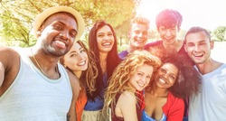Happy friends taking selfie at bbq picnic in nature park with back sunlight - Young people having fun with trends technology - Youth lifestyle, tech and friendship concept - Focus on african man face