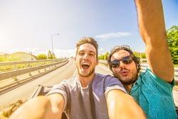 Happy friends taking selfie at car trip around Europe. Two caucasian men having fun on the road