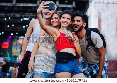 Happy friends taking selfie at music festival #1061179715