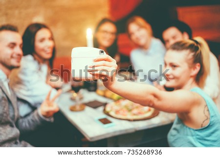 Happy friends taking selfie with instant camera in trendy cocktail bar restaurant - Young people having fun having appetizer before dinner - Youth technology concept - Vsco filter