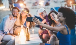 Happy friends taking selfie with smartphone at beach party outdoor - Young people having fun together at bar drinking champagne  - Focus on african girl hand phone - Youth and summer concept