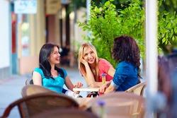 happy friends talking in summer cafe, urban outdoors