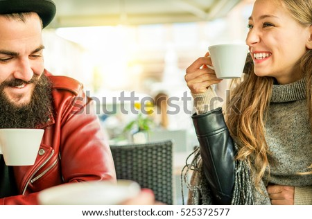 Happy friends toasting coffee and cappuccino at bar restaurant cafe  - Young hipster people enjoying breakfast drinking hot beverage - Friendship winter concept - Focus on woman eye - Warm filter
