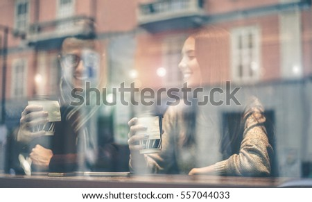 Happy friends toasting coffee in street city bar - People having a break sitting in cafe  drinking cappuccino - Reflection view from outside - Focus on woman right hand - Matte warm filter