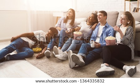 Happy friends watching comedy movie and eating popcorn, sitting on floor at home