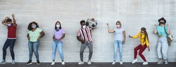 Happy friends wearing face mask listening music with vintage boombox outdoor - Multiracial young people having fun dancing together during corona virus outbreak - Youth millennial friendship concept