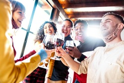 Happy friends wearing protective face masks toasting red wine sitting at bar restaurant - New normal friendship concept with young people having fun at home party - Focus on glasses