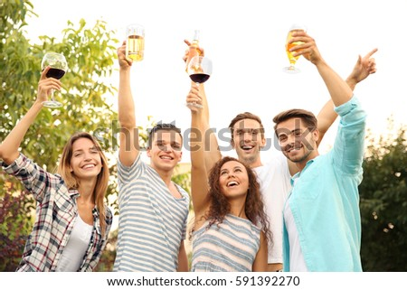 Happy friends with drinks having party outdoors #591392270