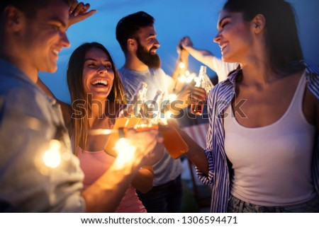 Happy friends with drinks toasting at rooftop party at night #1306594471