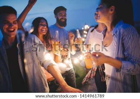Happy friends with drinks toasting at rooftop party at night #1414961789