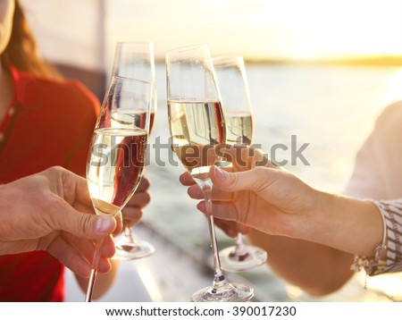 Happy friends with glasses of champagne on yacht. Vacation, travel, sea and friendship concept. Closeup. #390017230
