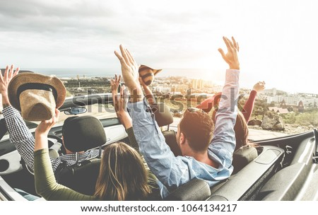Happy friends with hands up having fun in convertible car on summer vacation - Young people laughing and smiling together during travel holidays - Youth lifestyle concept - Main focus on right guys