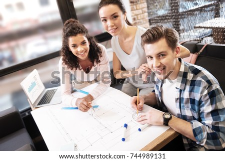 Happy friends working and making a technical drawing