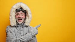 Happy frozen man in warm clothes has fun during winter points away on empty space wears gloves isolated on yellow background. Cheerful male adventurer with frosted beard and ski goggles has expedition