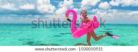 Happy fun beach vacation woman tourist ready to jump in ocean swimming with snorkel fins and pink flamingo toy pool float. Goofy swimmer girl running on holidays panoramic banner. Foto stock ©