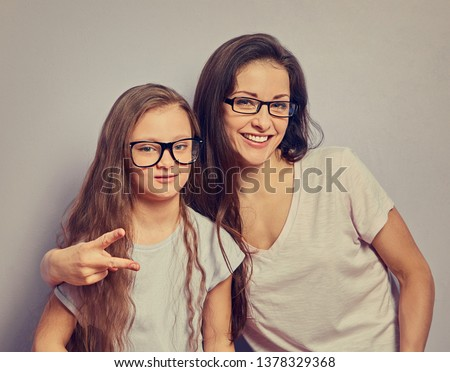 Happy fun young casual mother showing the horns sign two fingers and hugging her cute kid girl on violet wall background. Family in fashion eye glasses. Portrait vintage #1378329368