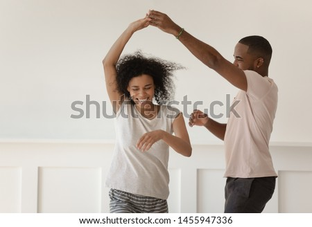 Photo of Happy funky young african american romantic couple holding hands dancing laughing at home, carefree active millennial black husband and wife wearing pajamas having fun bonding enjoy dance in bedroom