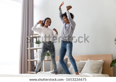 Happy funny african american family mom sister and teen daughter listening to music in headphones dancing on bed, excited active black mother with teenage girl jumping playing having fun in bedroom