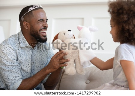 Happy funny african american father wearing crown holding toy having fun with cute small child daughter sit on sofa, cheerful black family dad and little kid girl laughing bonding playing at home
