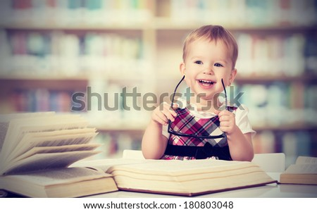 Happy funny baby girl in glasses reading a book in a library
