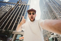 Happy funny bearded man taking selfie and showing thumbs up in Manhattan. Hipster tourist posing for photo while travel in New York.