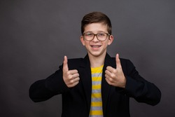 happy funny boy with glasses show gives a thumbs up and good luck. on a black, dark gray background.