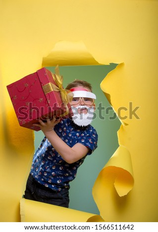 Happy funny child boy face portrait. Cool and confidant kid in sun glasses and Santa Claus shirt holding gift box. Christmas night. Happy xmas and New Year