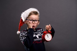 Happy funny child boy face portrait. Kid in glasses and Santa Clause shirt holding alarm clock. Christmas night. Happy xmas and New Year