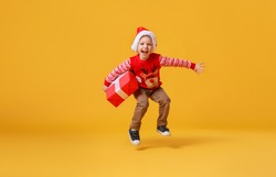 happy funny child boy in red Christmas reindeer costume jumping with gift on yellow colored background