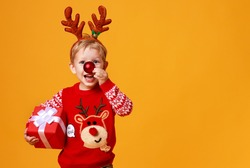 happy funny child boy in red Christmas reindeer costume with gift on yellow colored background
