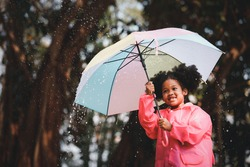 Happy funny child curly black hair with umbrella under the autumn shower. Girl is wearing pink raincoat and enjoying rainfall. Kid playing on the nature outdoors.