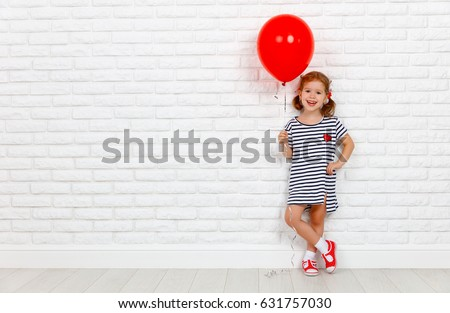Happy funny child girl with a red ball near an empty white brick wall