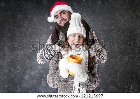 Happy funny couple  with a cup of tea covering  snow background.  Have a warm. Fool around.