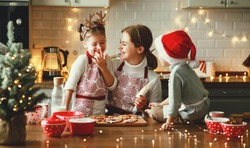 happy funny family mother and children  bake christmas cookies