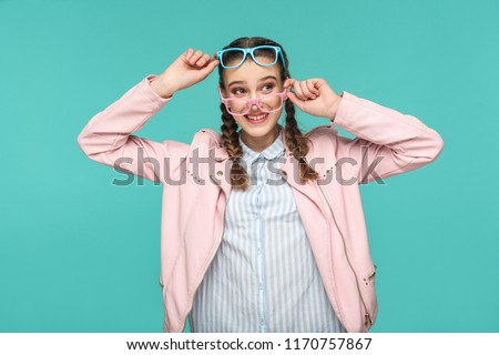 Happy funny girl in casual or hipster style, pigtail hairstyle, standing, holding two blue and pink glasses and looking away with toothy smile, Indoor studio shot, isolated on blue or green background