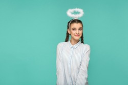Happy funny girl in striped blue shirt and pigtail hairstyle, standing with halo on her head and looking away with smile and dreaming face, Indoor studio shot, isolated on blue or green background