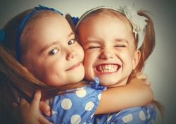 Happy funny girl twins sisters hugging and laughing