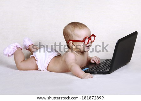 Happy funny kid with glasses is working at the computer