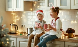 happy funny kids on Christmas eve, girl and boy laugh and drink hot cocoa drink that they baked together in cozy kitchen at home